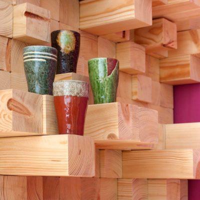 Detalle con vasos de cerámica de escultura mueble asimétrico con multitud de espacios y estanterías, de madera de abeto. Detail with mugs of sculpture-like furniture unit with multiple asimmetrical spaces and shelves.