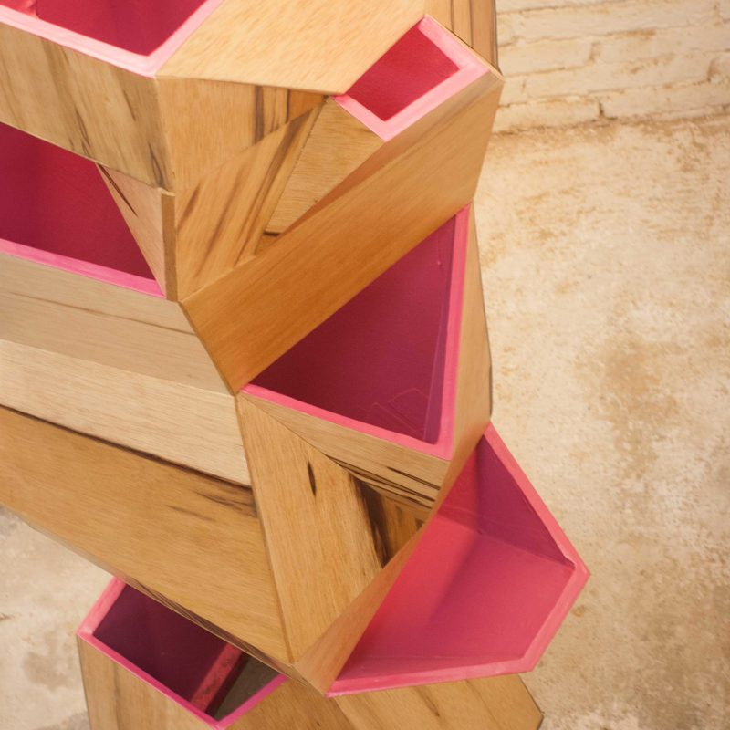 Close up of 7bocas faceted wooden sculpture with magenta interior