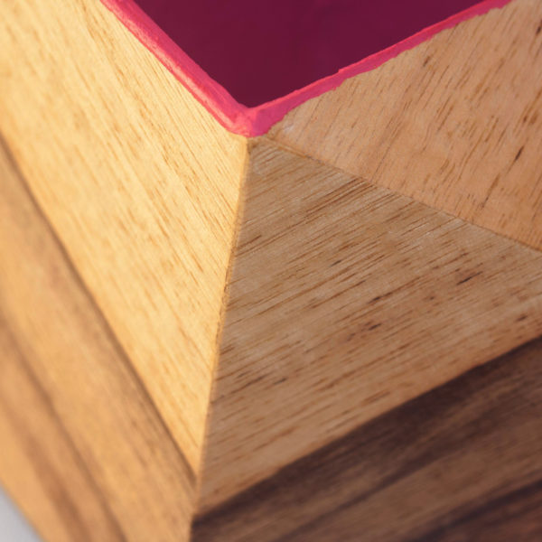 Close up of a faceted irregular plant pot, veneered with wood outside and magenta inside