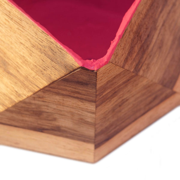 Close up of a faceted regular plant pot, veneered with wood outside and magenta inside