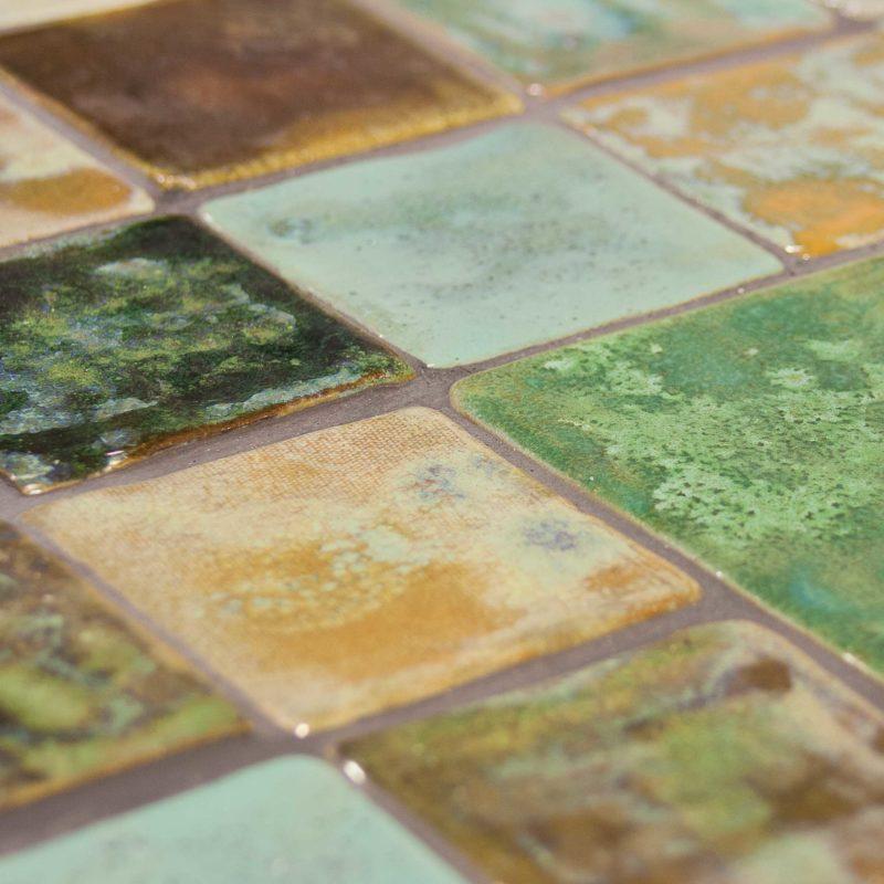 Detalle de mesita de estructura metálica y baldosas hechas a mano tonos verdes. Close up of low coffee table made of steel and handmade green tiles.