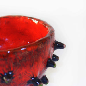 Close up of a blowfish-like spiky handmade red ceramic bowl